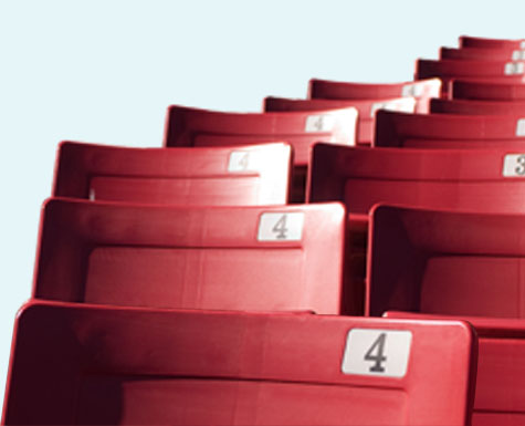 Red stadium seats located at an outdoor sports and entertainment venue. Sharp focus upfront with background seats blurred.