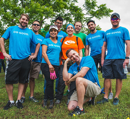 UFCU employees pose for a photo after helping plant some trees.