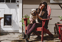 Genest and her dog enjoy the porch on the home she purchased with the help of a UFCU mortgage loan.