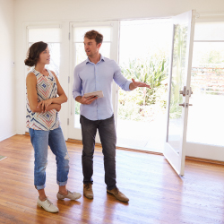 Male Realtor Showing Female Client Around House