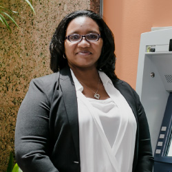 Latasha stands next to an ATM in our corporate offices.